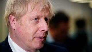 """Prime Minister Boris Johnson speaks to staff and students during a visit to Bolton University chancellor""""s building after a huge blaze damaged a block of student accommodation flats in Bolton on Friday evening"""