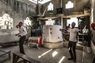 Churchgoers pray inside Eglise Evangelique Baptiste church