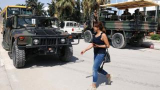 A woman walks past army soldiers outside a sports hall where ballot boxes and election material are collected to be distributed to polling stations, ahead of Sunday's presidential election in Tunis (14 September 2019)