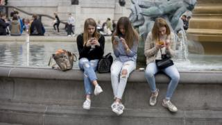 Three teenage girls are lost in the world of smartphone apps and messaging, in Trafalgar Square. While in a very busy environment, the capital's main square in central London, the teenagers obsessively tweet and message their friends at home, completely unaware of their surroundings, absorbed in the functions of their devices and their young lives. Sitting on the walls of the fountains, they are isolated from each other and the noise around them. In the backgrounds are tourists enjoying the arch