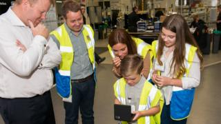 Thomas sees his design for the first time, together with his family and Royal Mint staff