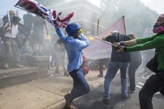 A White Supremacist tries to strike a counter protestor with a White Nationalist flag during clashes at Emancipation Park where the White Nationalists are protesting the removal of the Robert E. Lee monument in Charlottesville, Va., USA on August 12, 2017.