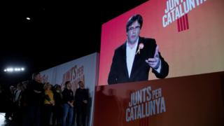 "Ousted Catalan leader Carles Puigdemont appears on a screen during an event of his political platform ""Junts per Catalunya"" to mark the official start of the electoral campaign"