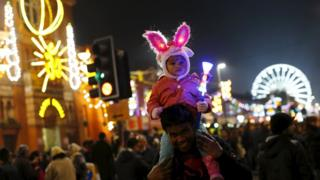 A girl sits on her father's shoulders after the switching on of Diwali lights in Leicester