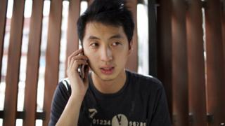 Hong Kong photojournalist Hok Chun Anthony Kwan speaks on the phone after leaving Samut Prakan provincial court after he was released on bail Monday, Aug. 24, 2015