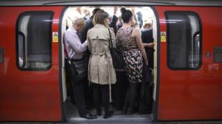 Commuters travel on a crowded Northern Line tube train of the London Underground