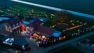 An aerial shot of a house and garden heavily decorated with Christmas lights and illuminated models.