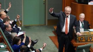 Australian Prime Minister Scott Morrison and several government MPs raise their hands in the House of Representatives