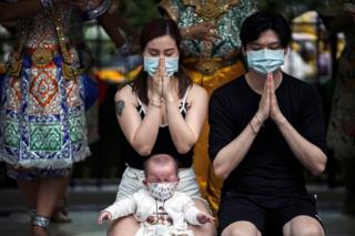 Chinese tourists wearing protective masks pray at the Erawan Shrine in Bangkok, Thailand.