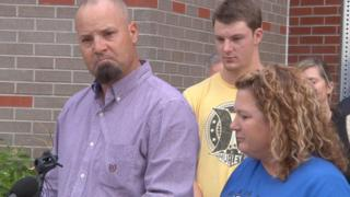 In this image taken from AP Video, David Schemm, left, makes a statement to reporters outside Swedish Hospital in Englewood, Colo., as his son, Clay, center, and wife Lisa look on during a news conference Wednesday, Nov. 4, 2015.