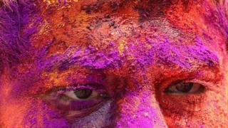 A close-up of a face covered in coloured paint powder