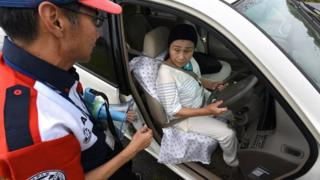 older woman in car driving seat, being taught by man