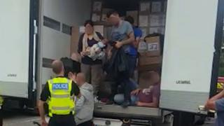 A police officer speaking to a group of migrants, including a woman holding a baby, in the back of a lorry at Watford Gap services.