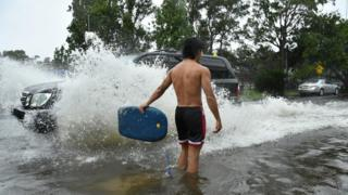 A car passes a man standing in flood water in Sydney, Australia (9 Feb 2020)
