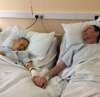 Mike Bennet, 57, and wife Julie, 50, from Irby in Wirral, holding hands in a hospice