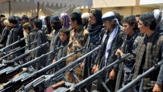 A line of IS members in front of weapons