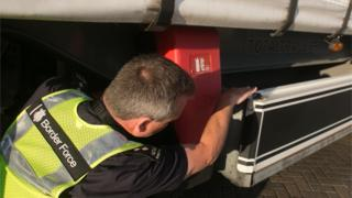 Border Force staff check underneath a lorry
