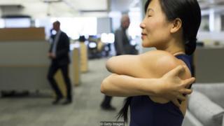 Một hướng dẫn viên thể dục dạy cho nhân viên văn phòng các kỹ thuật yoga ở Toronto