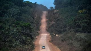 Cars on a clay road in the Amazon