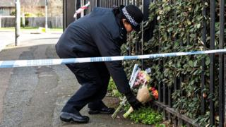 Police officer places flowers at scene of fatal stabbing in London