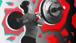 A woman lifts weights at a Cross Fit class