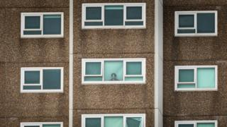 in_pictures A woman in one of the locked-down public housing towers in Melbourne's west stares out the window