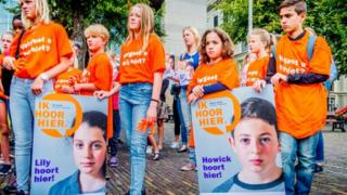 Children hold placards that say Howick and Lily belong in the Netherlands