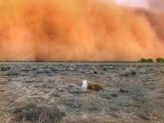 A child running towards a dust storm in Mullengudgery in New South Wales