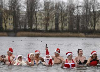 Members of a swimming club take their traditional Christmas bath at the Orankesee lake in Berlin