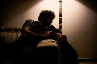A man sits on his sofa with his guide dog