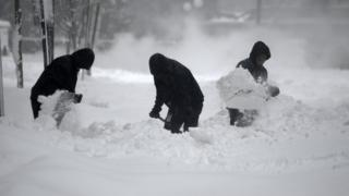 Workers clear snow from a pavement in Washington DC in the US