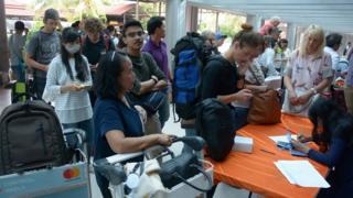 滞留巴厘岛的旅客挤在询问处查询航班状况。