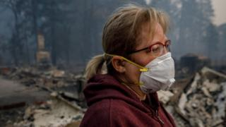 Woman wearing a smoke mask in northern California after deadly fires