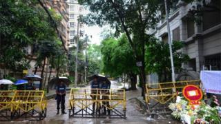 Bangladeshi policemen stand under umbrellas at a checkpoint in Dhaka