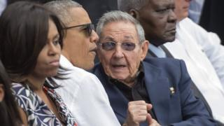 US President Barack Obama (centre) talks to Cuban President Raul Castro (right) as they - together with Michelle Obama (left) attend a baseball game in Havana