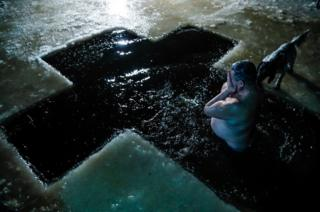A man takes a dip in icy water during celebrations for the Orthodox Epiphany