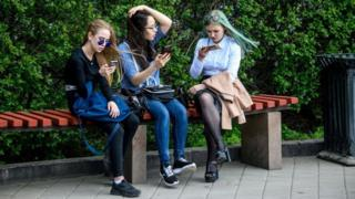 Young people looking at their phones