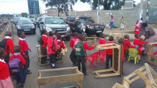 Pupils of Kenyatta Golf Course Academy, Nairobi block Mbagathi Road with their desks after their school was demolished.