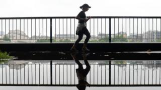 A girl runs thru a puddle on the South Bank in London