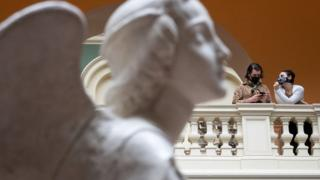 Two women wear masks as they chat with a marble statue in the foreground