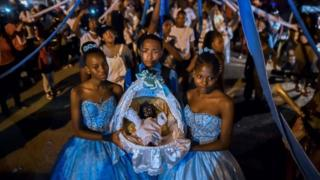 """Afro-Colombians hold a basket with """"Nino Dios"""" (God Child) inside in Quinamayo, department of Valle del Cauca, Colombia, on February 18, 2018."""
