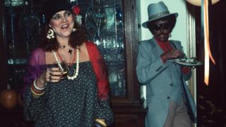 Joni Mitchell (right), in blackface, at a party with Henry Diltz's wife