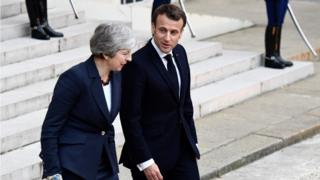 French President Emmanuel Macron (R) accompanies out British Prime Minister Theresa May after a meeting at the Elysee Palace in Paris on Tuesday