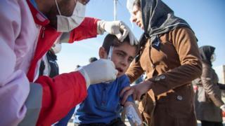 Un socorrista atiende en medio de la calle a un niño herido por el terremoto