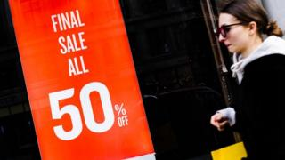 Woman walking past shop window advertising a sale