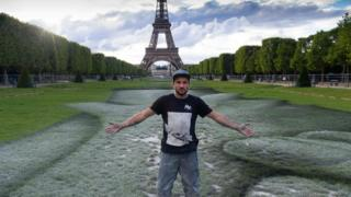 French street artist Saype poses at the Eiffel Tower in front of his giant artwork
