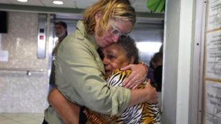 Puerto Rico's mayor holds an upset elderly woman after Hurricane Maria