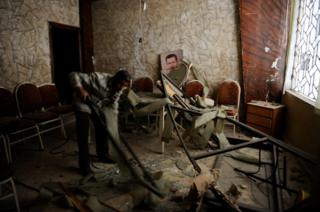 A man cleans a damaged room with a picture of Syria's president Bashar al-Assad