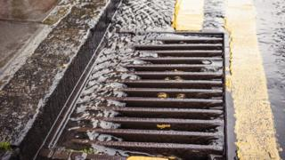 A stream of rainwater flowing down the tarmac of a street, into a gutter