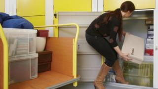 woman putting things in storage